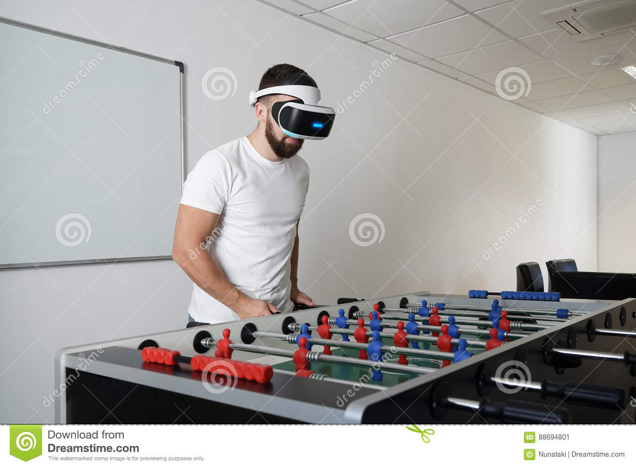 Man in virtual glasses playing at office in table soccer