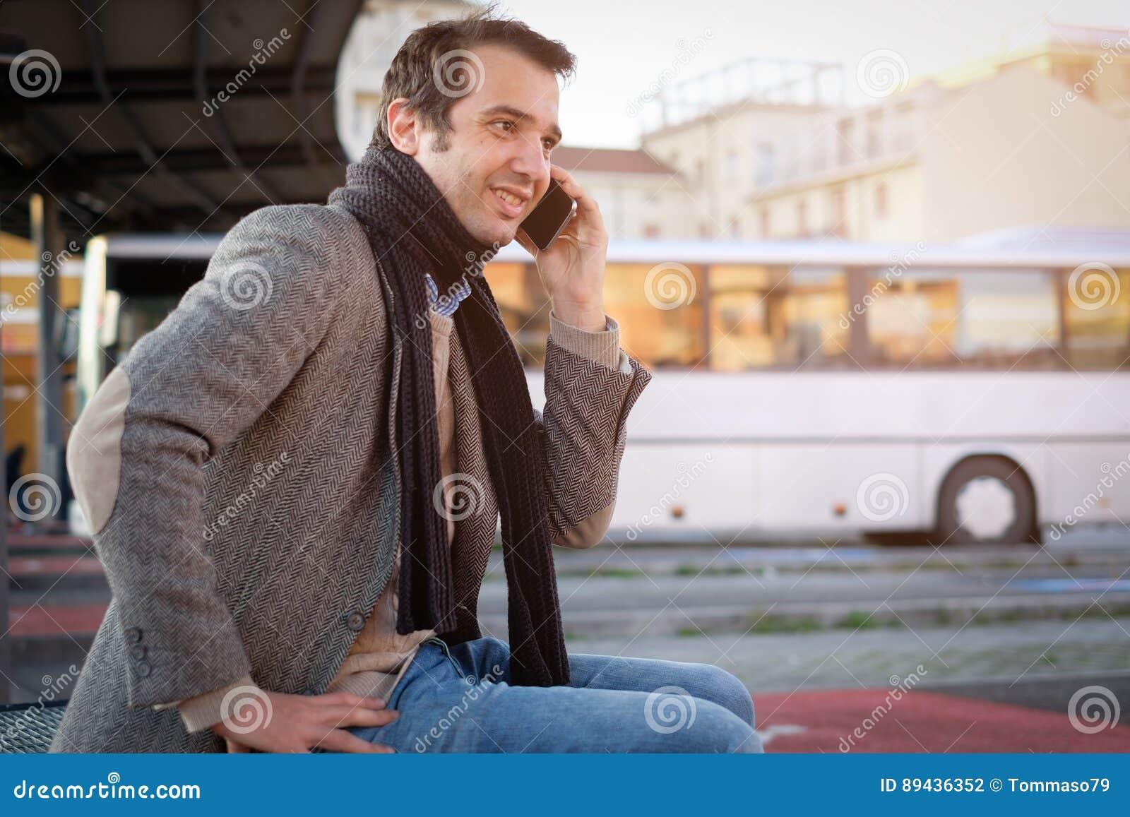 Man waiting at the bus station and talking