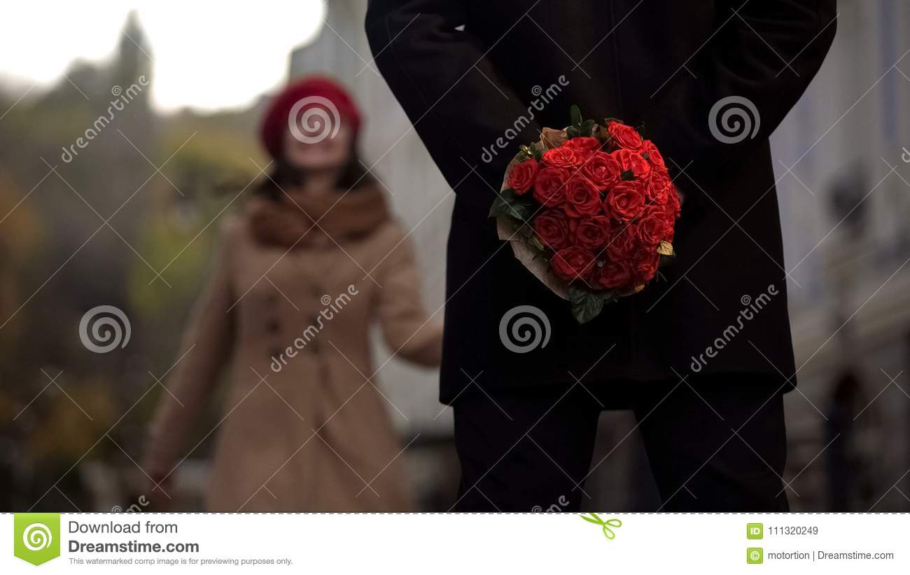 Man waiting for girlfriend, holding flowers, first date, beginning of relations