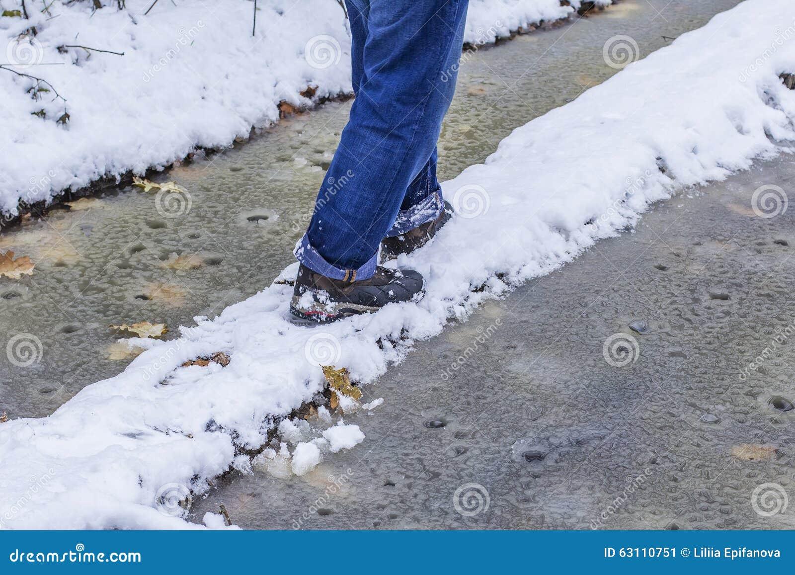 man walking along a narrow path perilous winter at wet weather