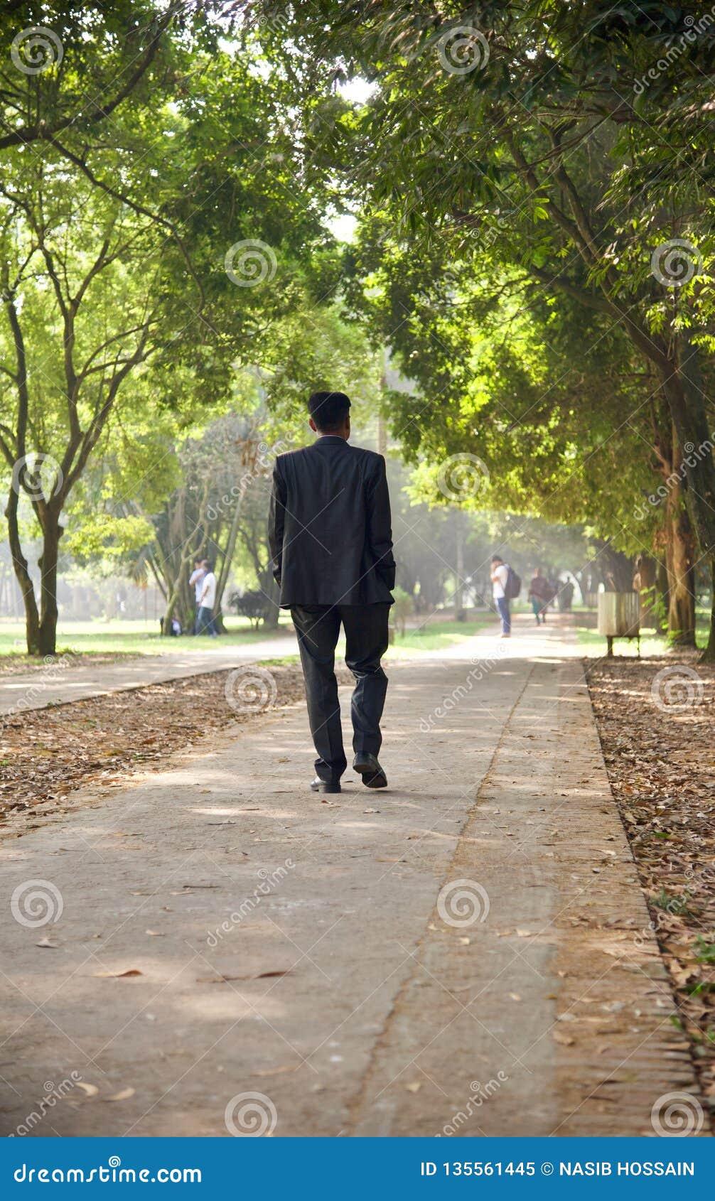 A man walking around a park way unique photo