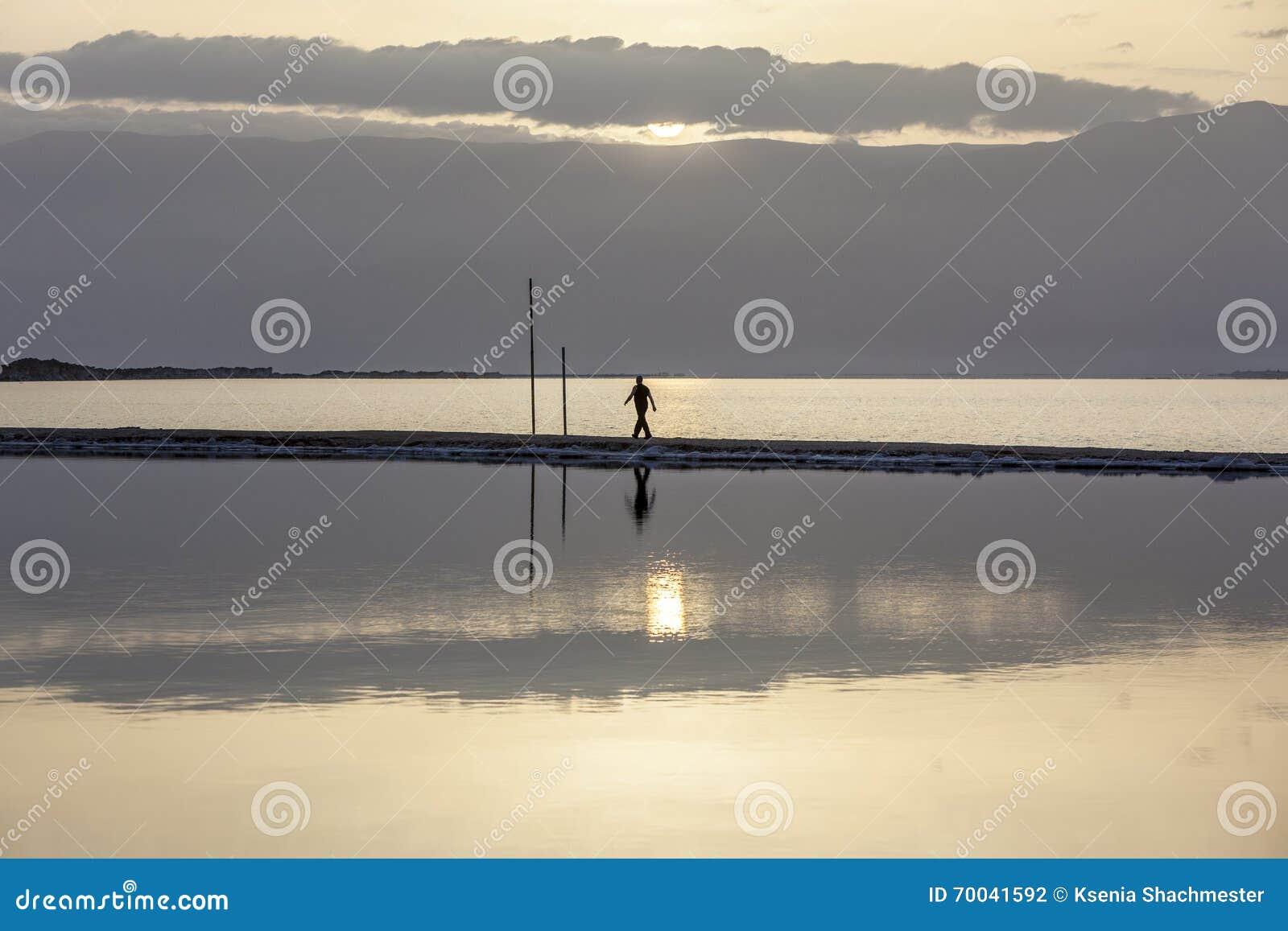 Man walking on headland at early morning under rising sun