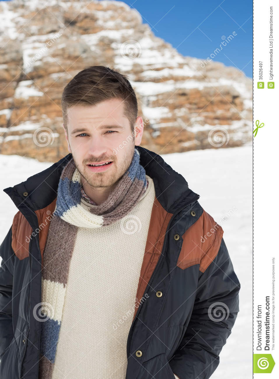 Man In Warm Clothing Standing On Snow Covered Landscape