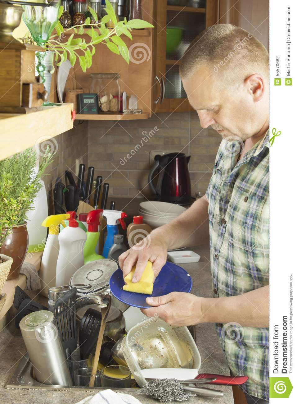 man washing dirty dishes in the kitchen sink  stock photo