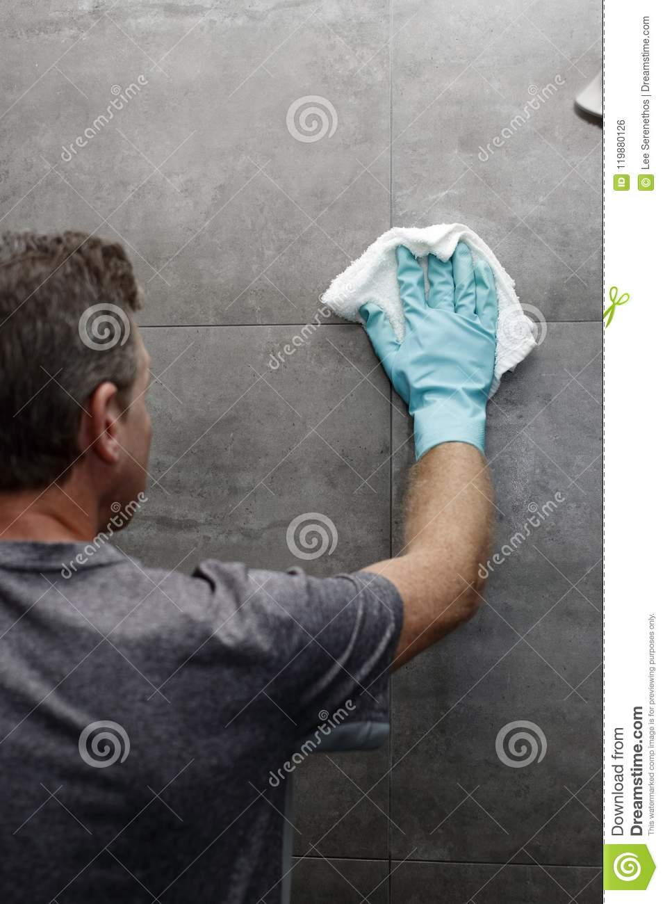 Man Washing Shower Wall with a Rag While Wearing a Green Protect
