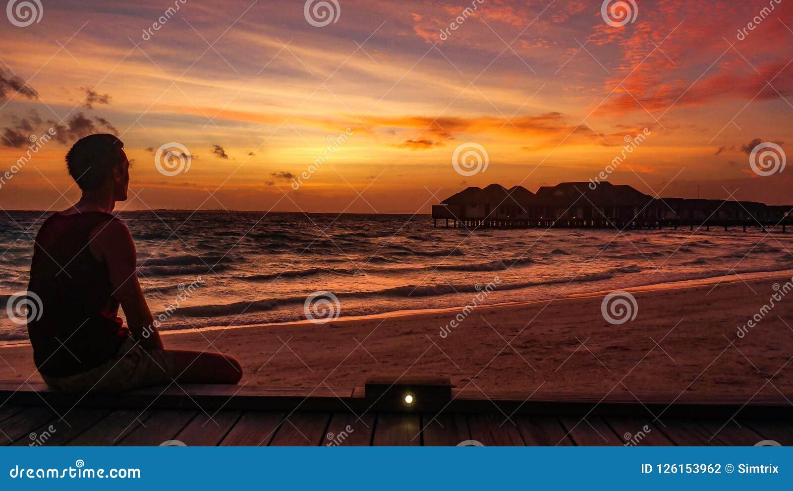 Man watching Beautiful Sunset over the Indian ocean on Maldives Resort Island.