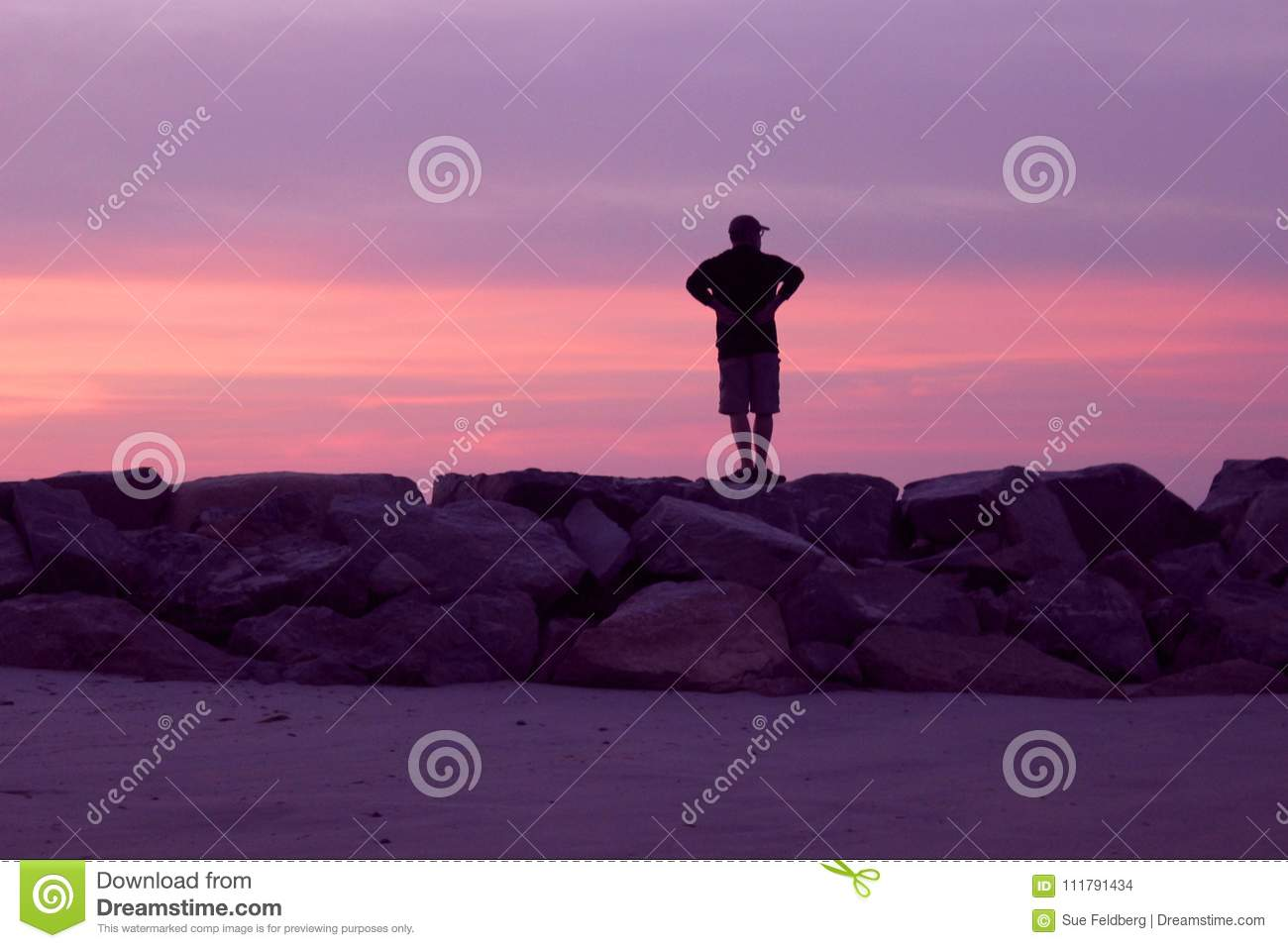 Man Watching a Pink and Violet Sunset at the Beach
