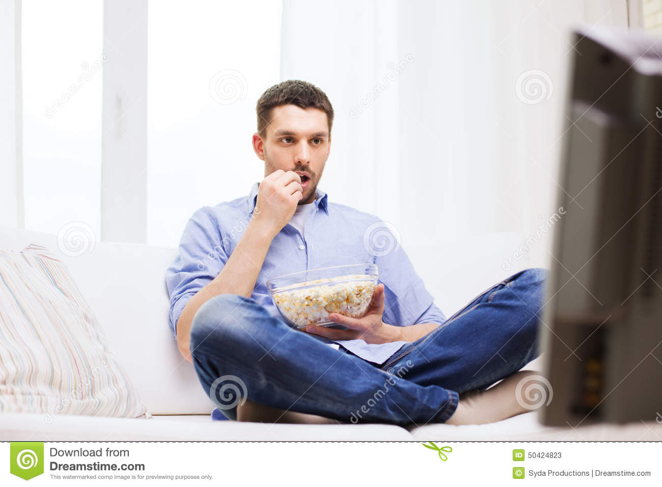 Man watching tv and eating popcorn at home stock photo for People watching