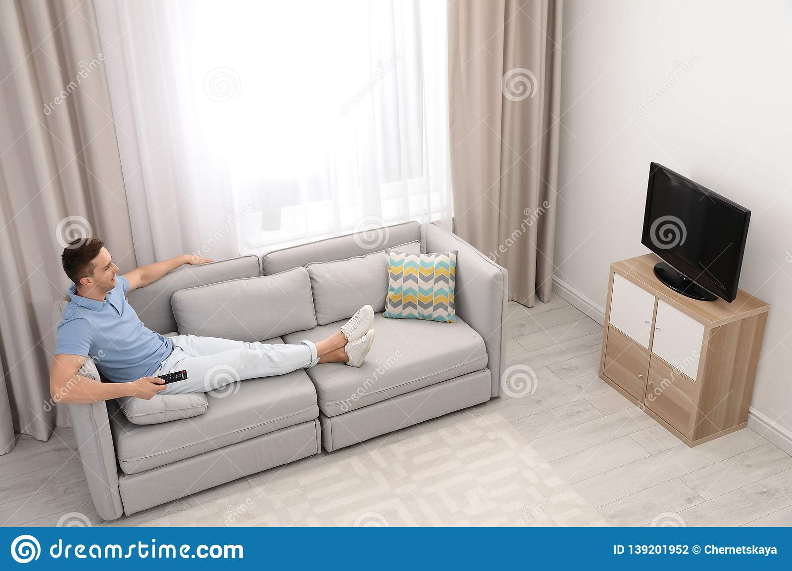 Man Watching Tv On Sofa In Living Room View From Above Stock Photo