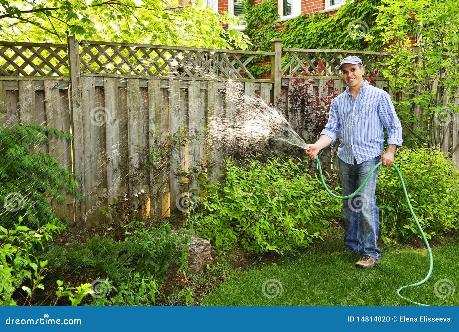 Backyard Garden Irrigation : Man watering garden stock photo image