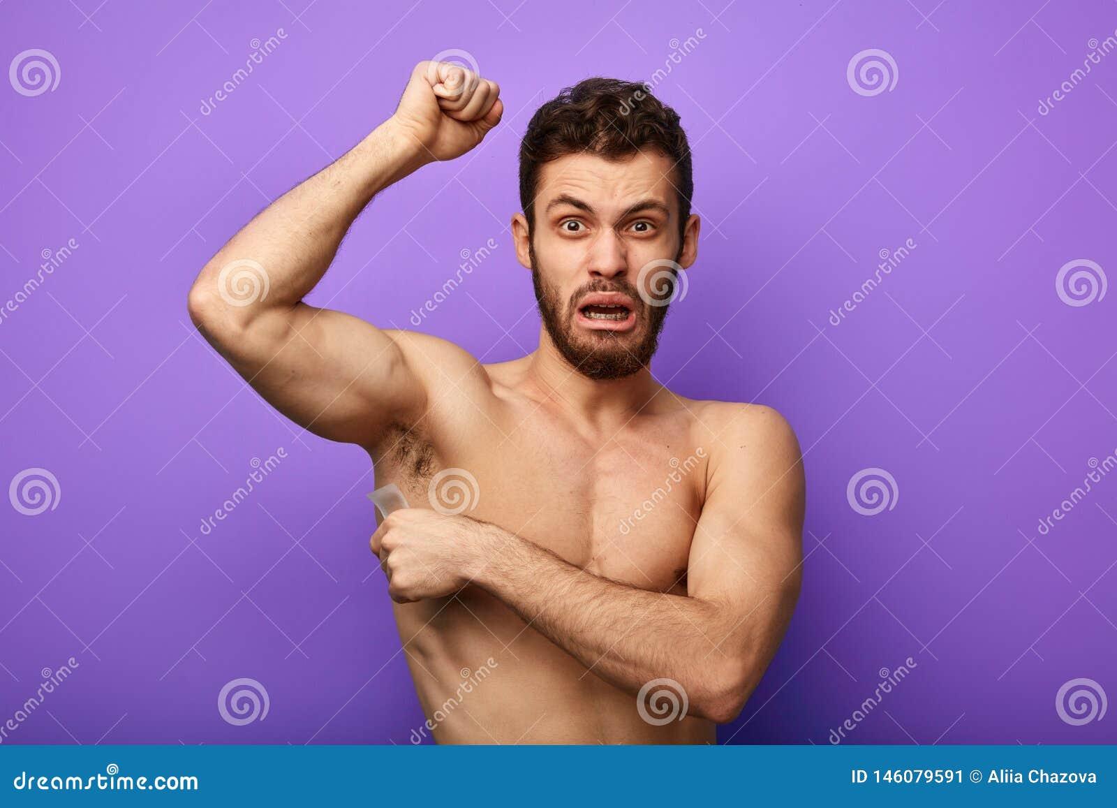 Man waxing his armpits to depilate hair