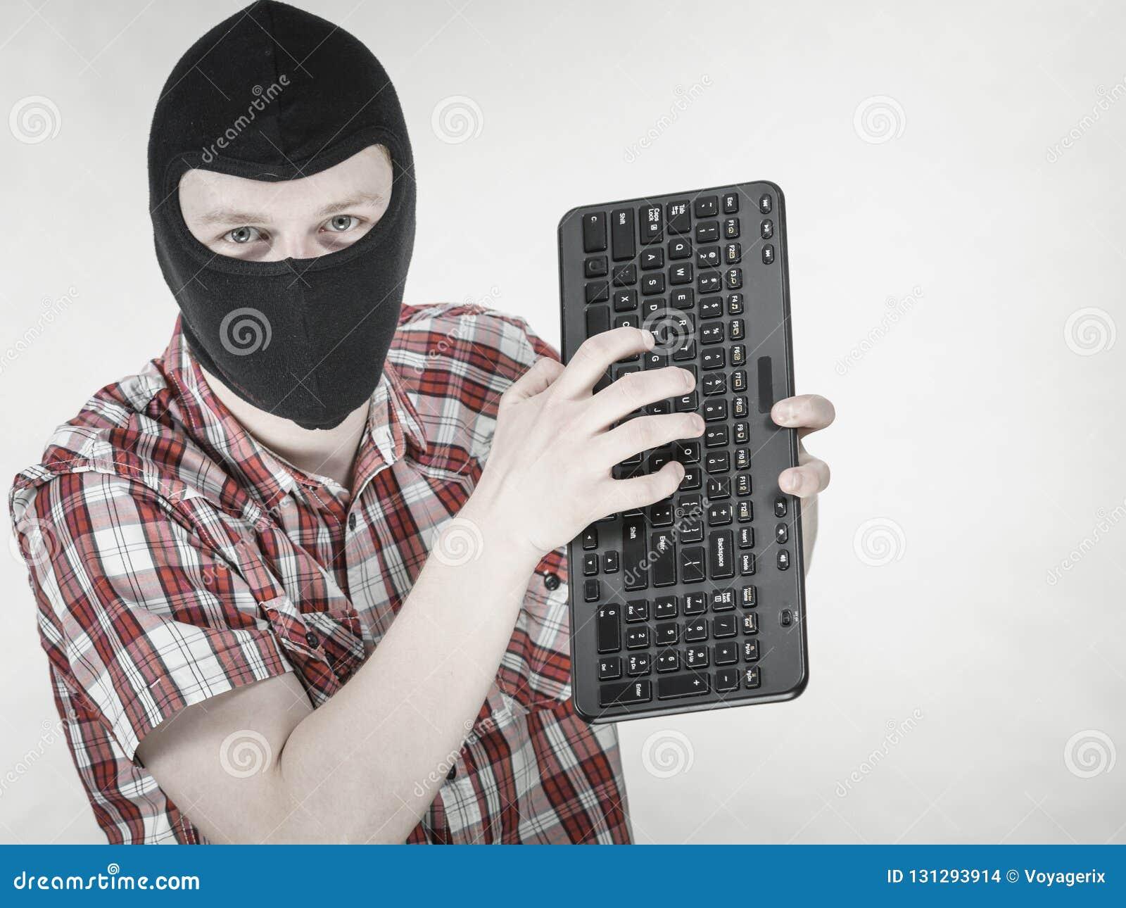 Man wearing balaclava holding keyboard