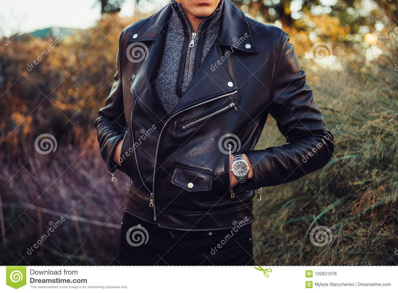 Man wearing black leather jacket and watch posing outdoors