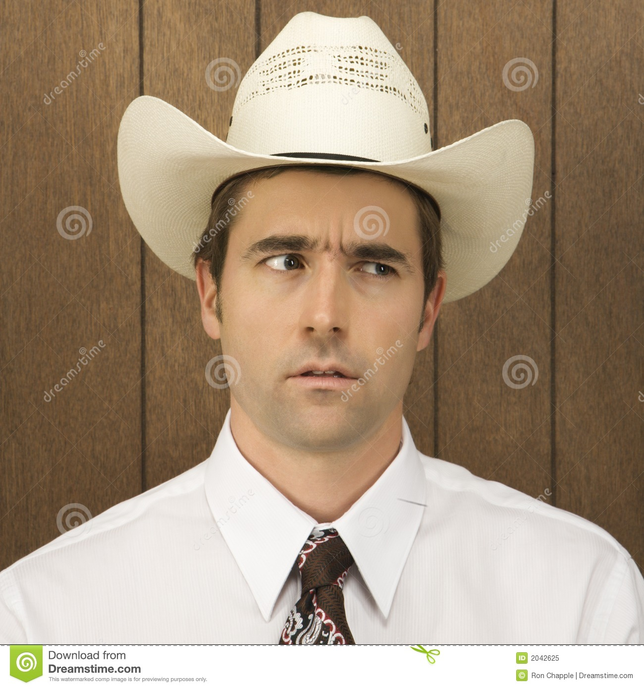 Man wearing a cowboy hat lookinig off to side. Mid-adult Caucasian male  wearing 6e84e74fb1a9