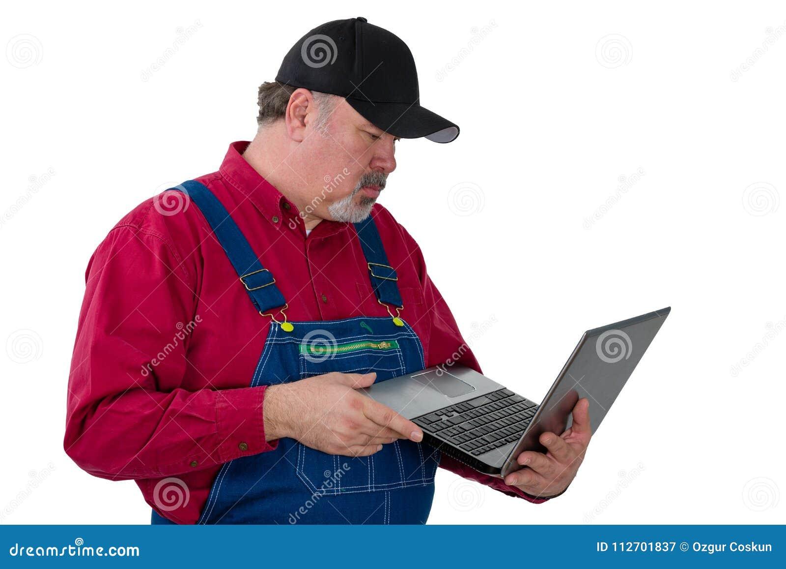 Man wearing dungarees holding laptop