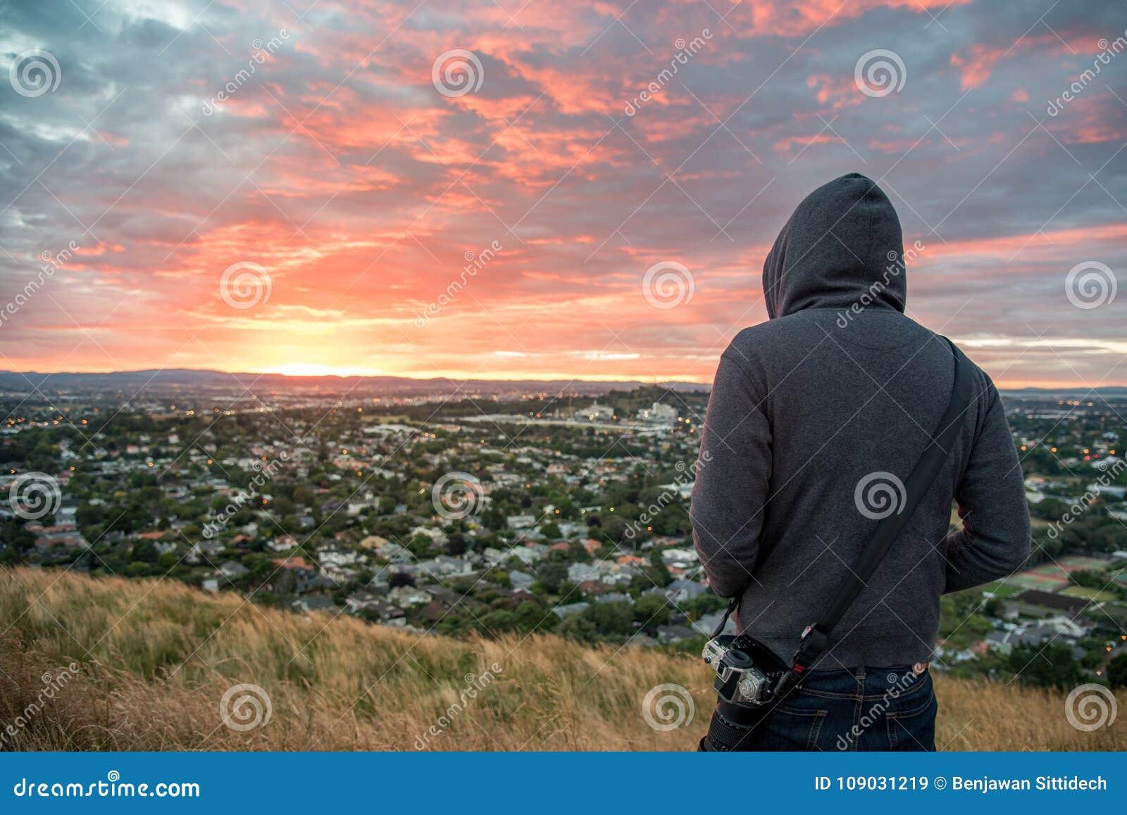 Man wearing hoody watching sunrise over Auckland city