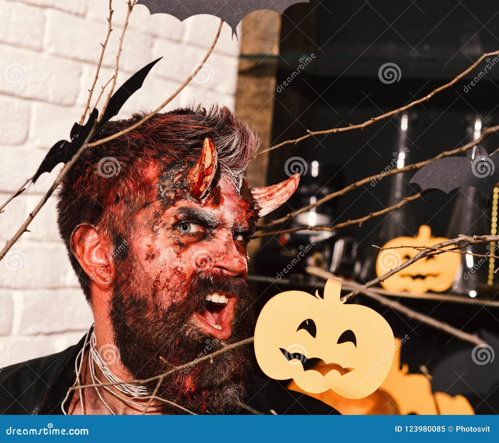 man wearing scary makeup with halloween pumpkins and bats decor