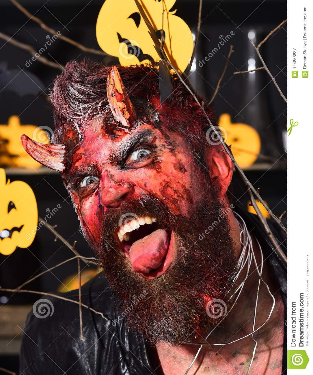 man wearing scary makeup with halloween pumpkins and bats decor