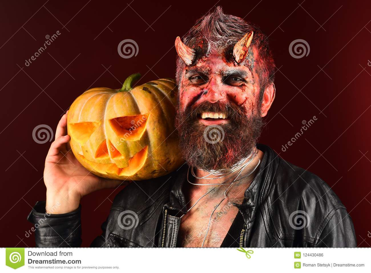 Scary Halloween Makeup For Guys With Beards.Man Wearing Scary Makeup Holds Pumpkin On Bloody Red