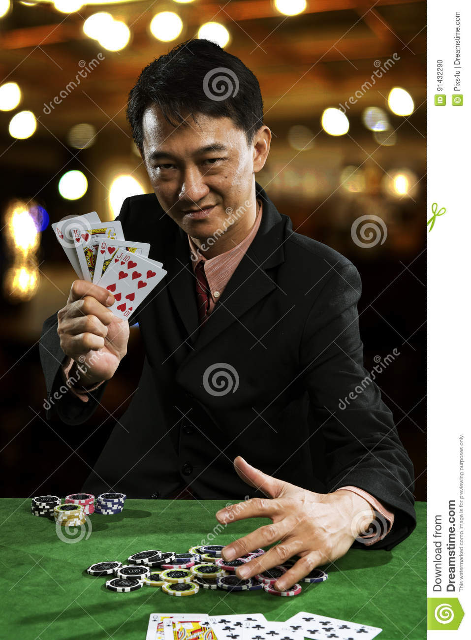 A man wearing a suit holding Hearts Suit Straight Flush