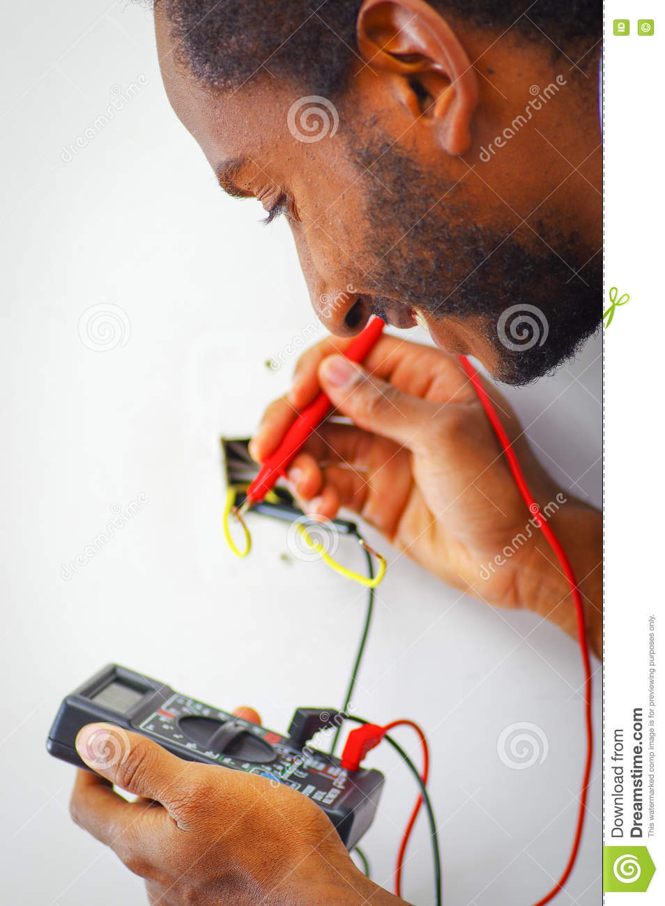 Man wearing white and blue shirt working on electrical wall socket wires using multimeter, electrician concept