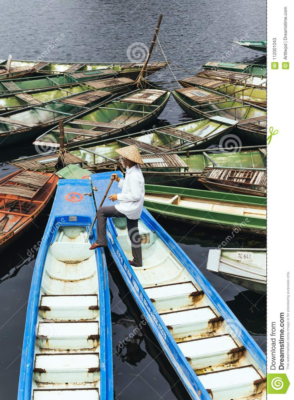 Man wearing white shirt, conical hat with his paddle stand on blue empty boat with many boats stop over the river.