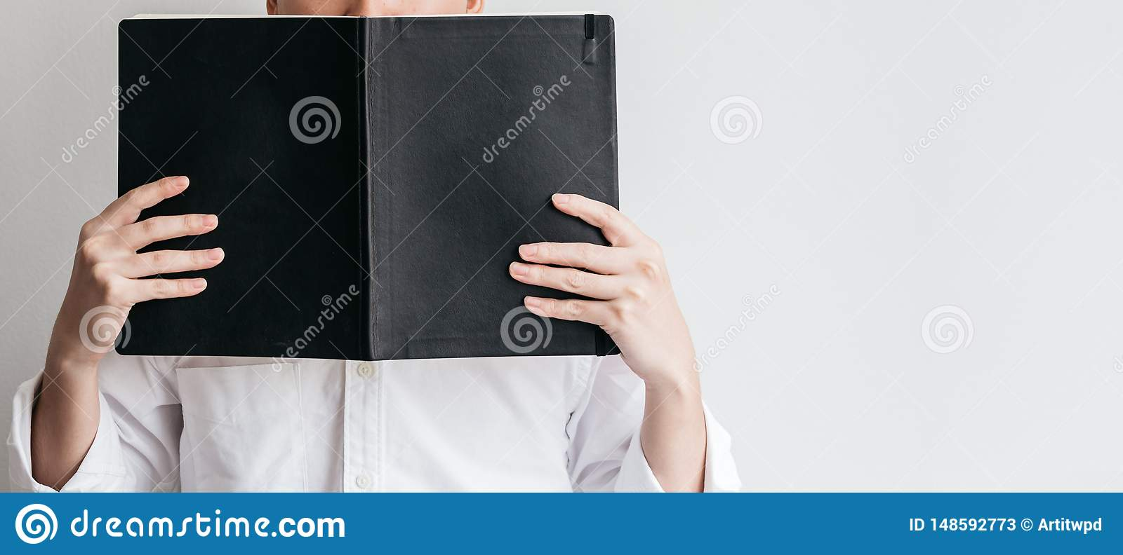 Man wearing white shirt and holding a black cover book in front of him on the left side with copy space