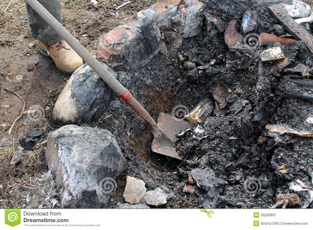 Cleaning Fire Pit : Man in workboots cleaning out fire pit with shovel stock
