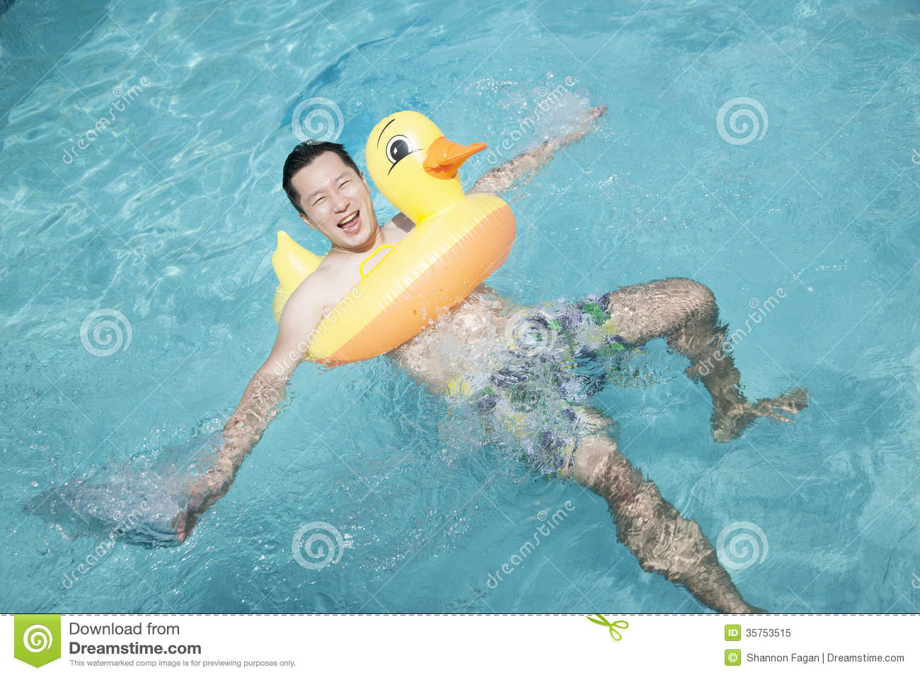 Man Wearing A Yellow Duck Inflatable Tube And Playing In