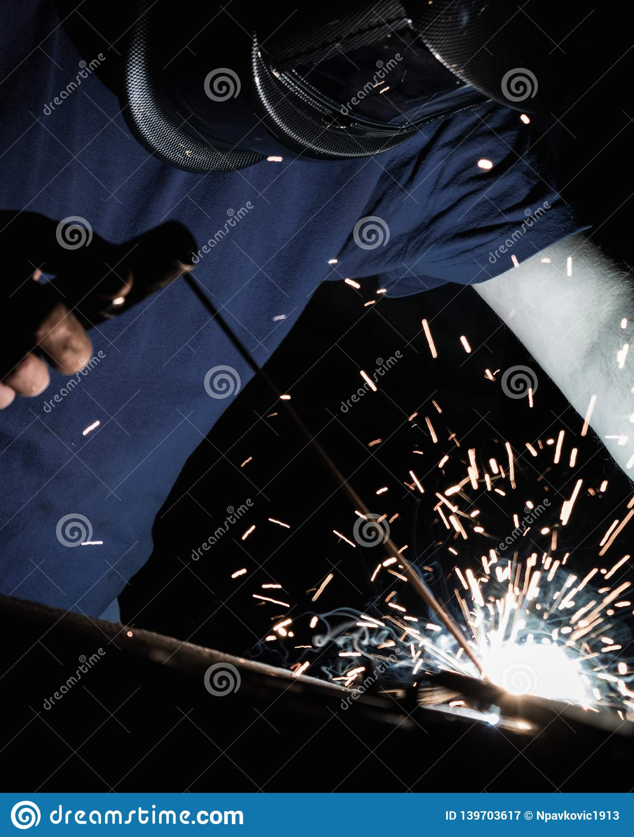 Man welding iron with a protective mask