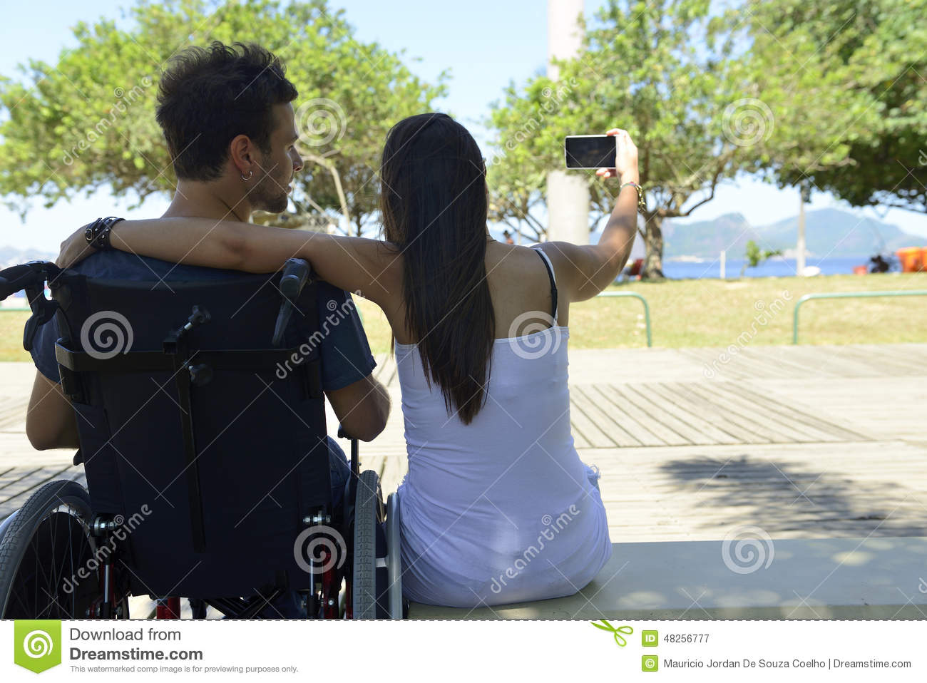 Man in wheelchair and girlfriend taking selfie
