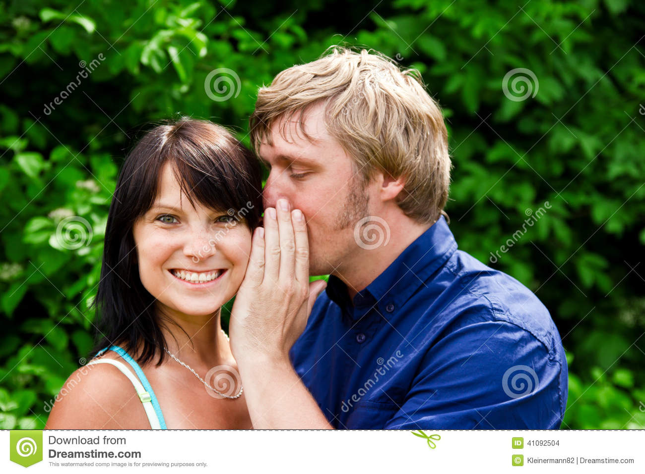 man whispering into the womans ear stock photo image of