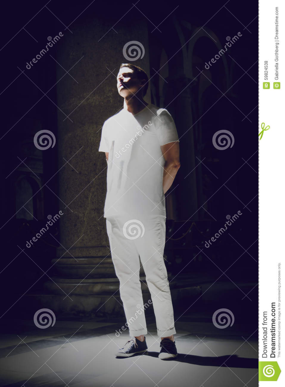 Man in white flooded in light from the ceiling window of a church.