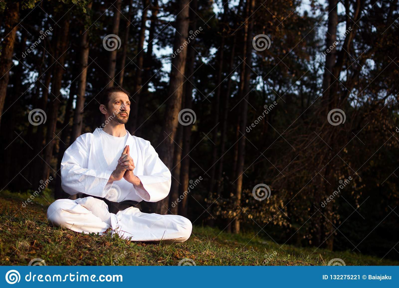 Young woman resting in a forest sitting in meditation