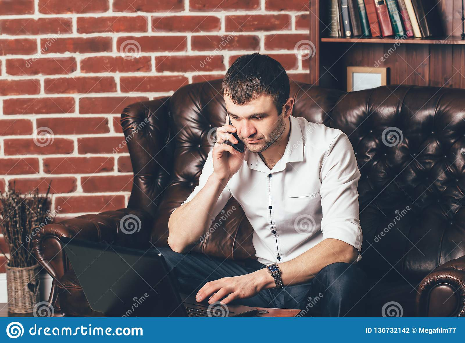 A man in white shirt talks on the phone. Businessman sits on a leather sofa behind his laptop on the background of a shelf with