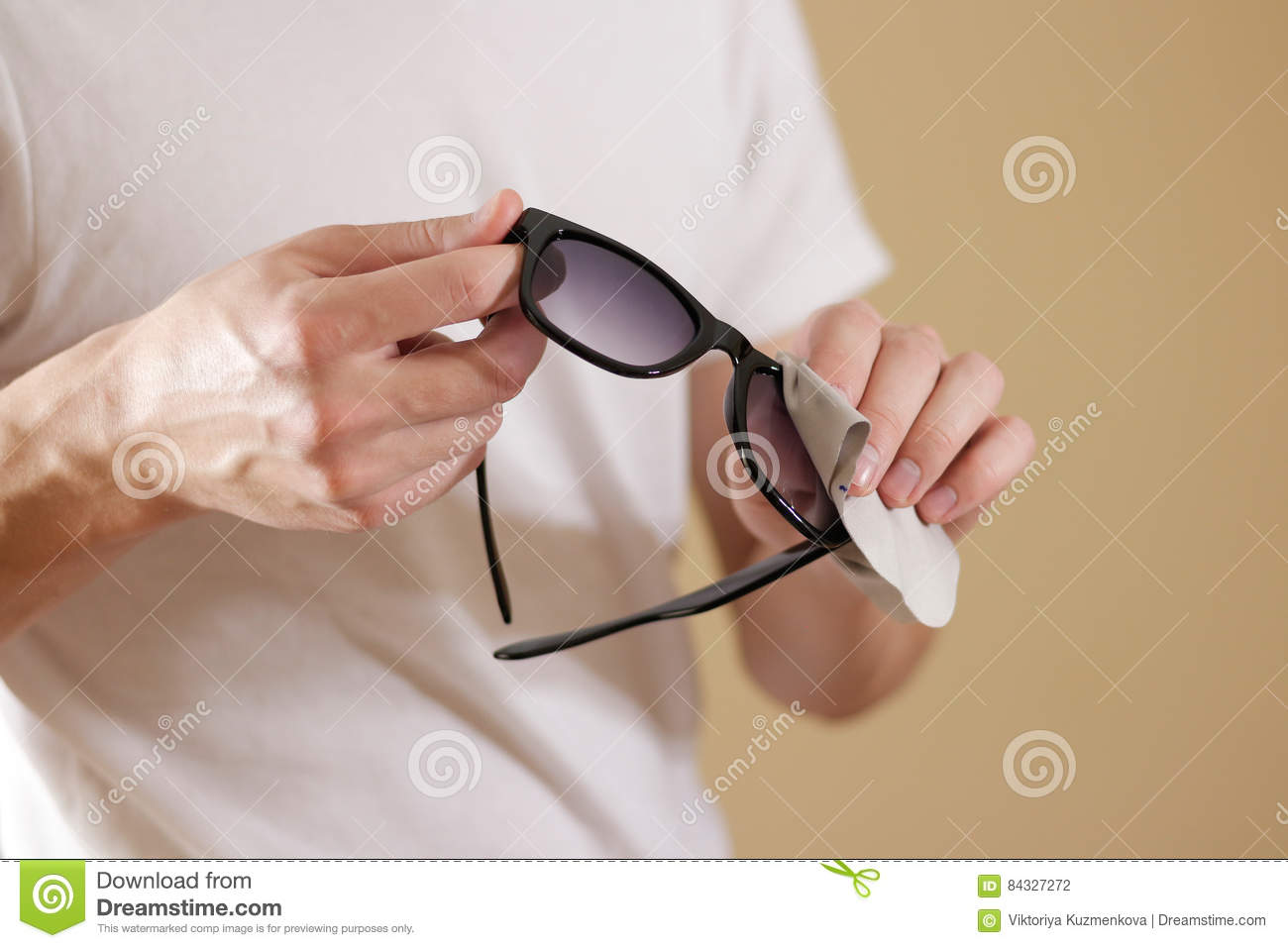 534a9792df Man in white t shirt hand cleaning black sun glasses lens with background