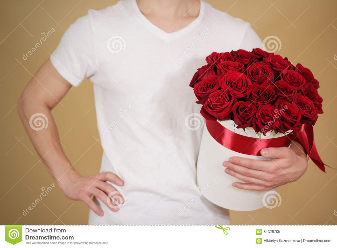 Man in white t shirt holding in hand rich gift bouquet of 21 red