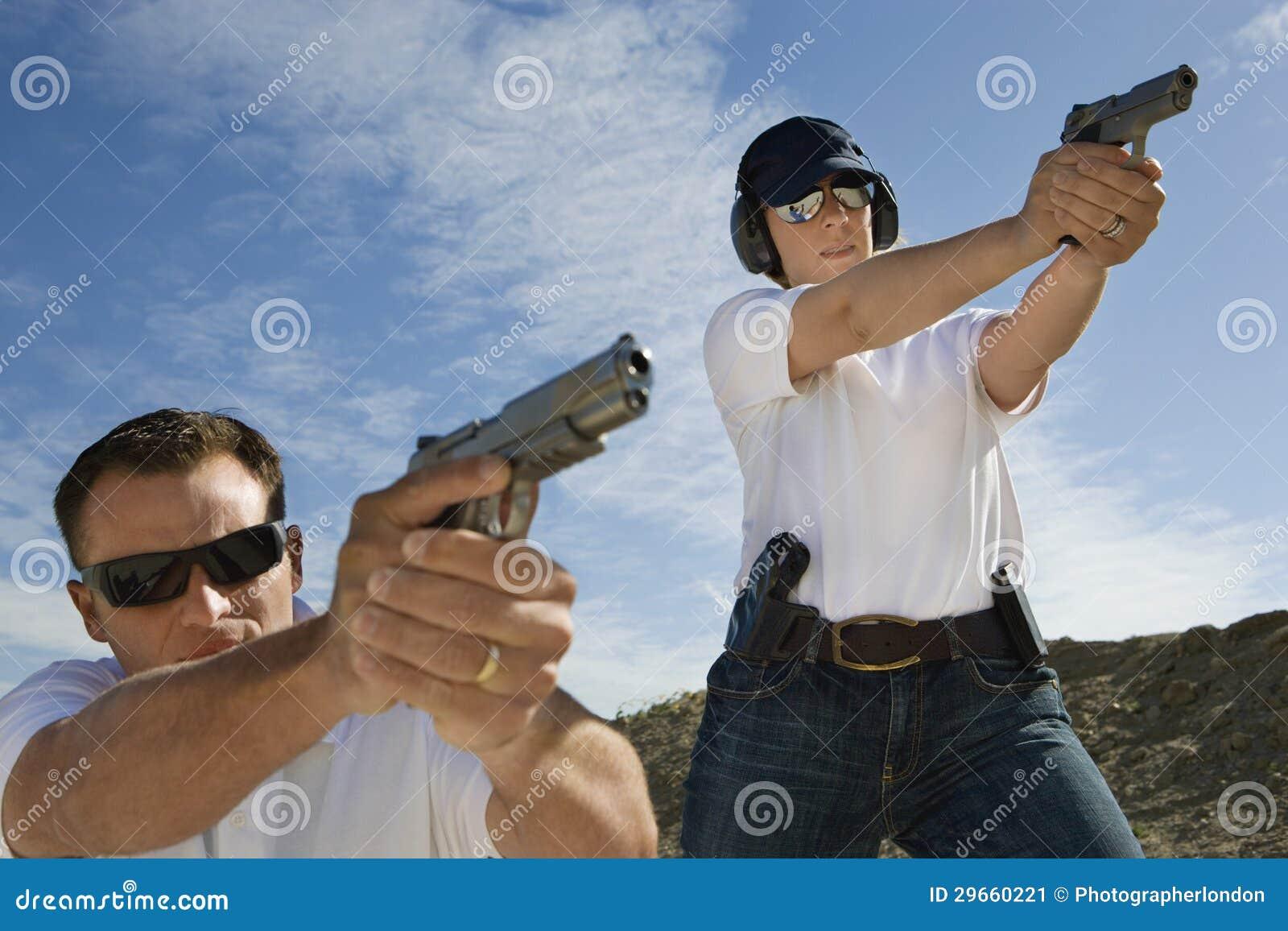 man and woman aiming hand guns at firing range stock image