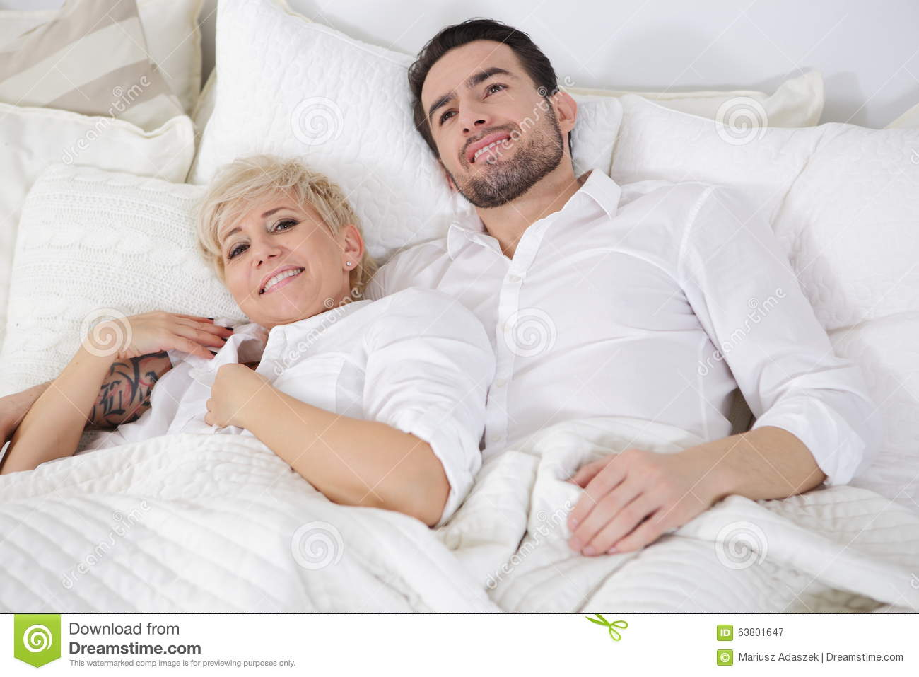 Couple on bed touching and groping one another