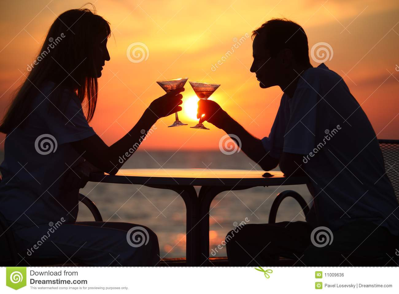 Man And Woman Clink Glasses On Sunset Outside Stock Photo