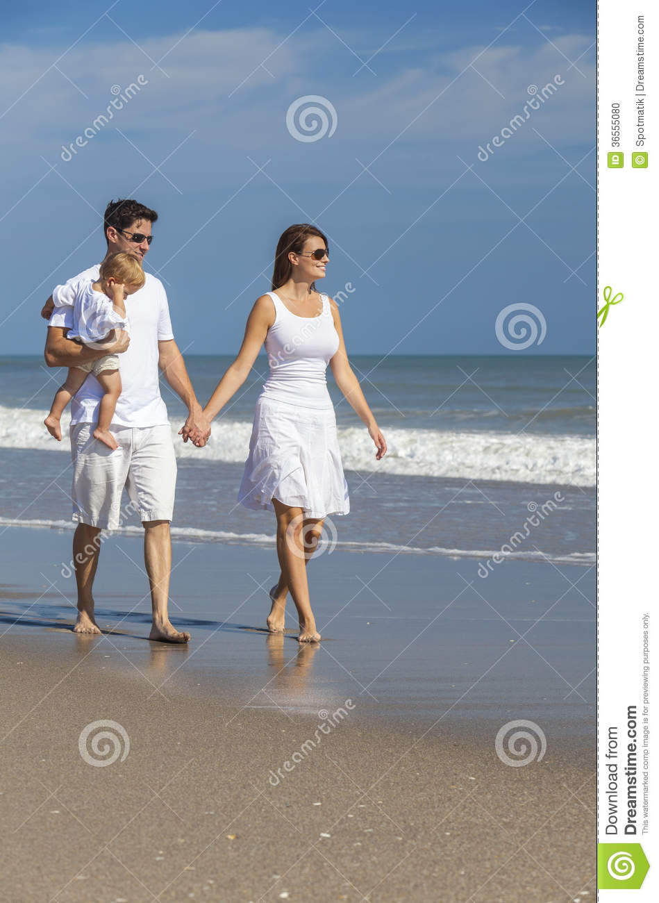 42054c0b2f51 Man and women romantic couple in white clothes holding hands walking  holding baby child on a deserted tropical beach with bright clear blue sky