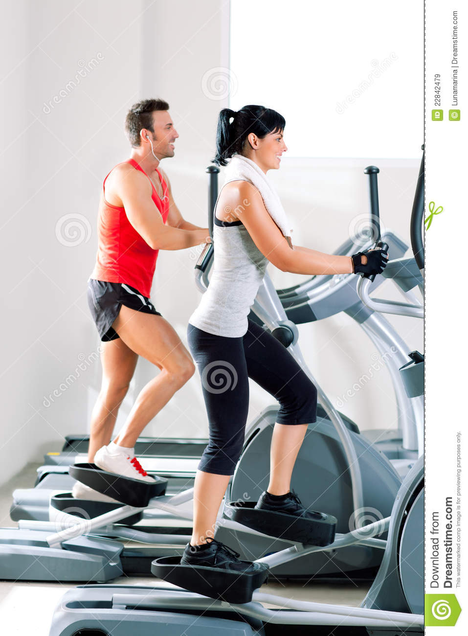Man and woman with elliptical cross trainer at gym royalty for Gimnasio sport gym