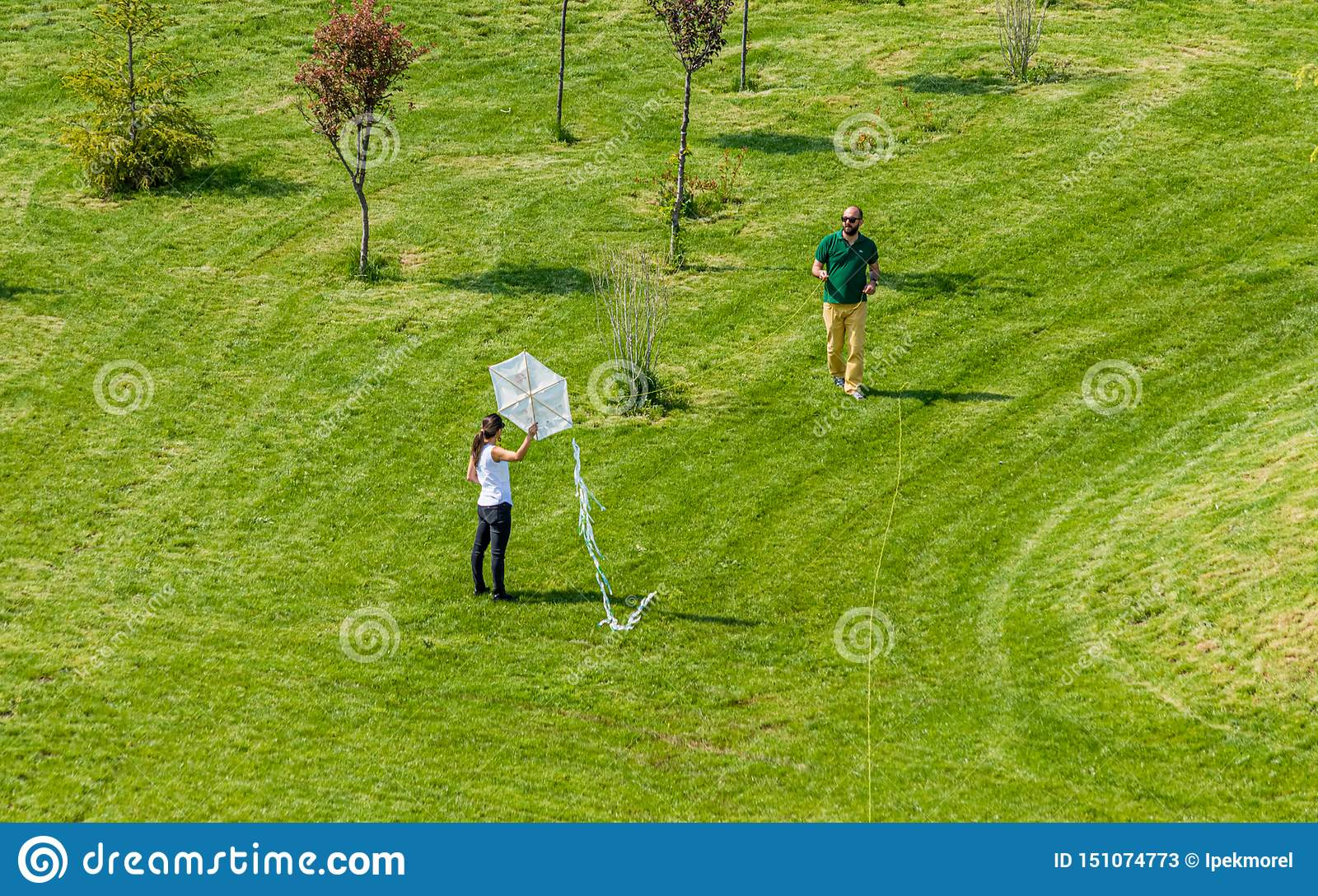 Man and woman flying a white kite in a park