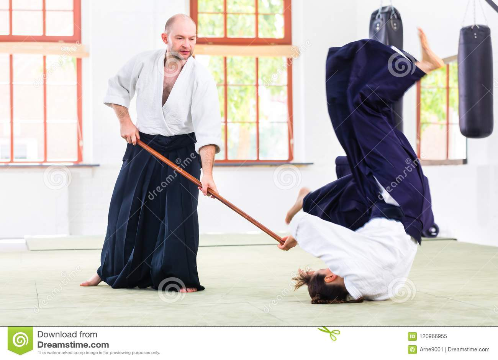 Man and woman having Aikido stick fight