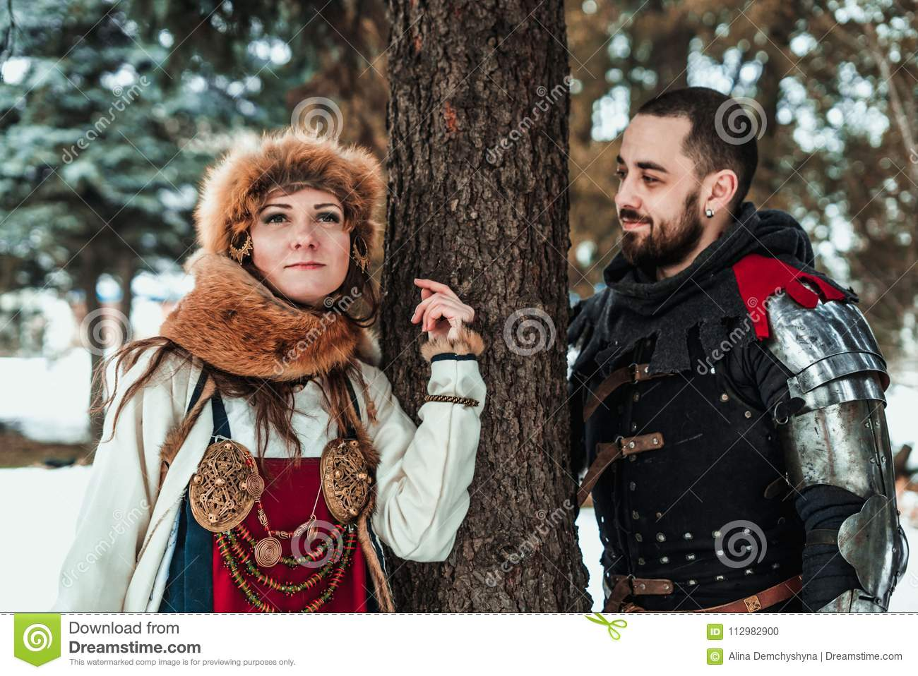 A man and a woman in historical costumes stand near a tree
