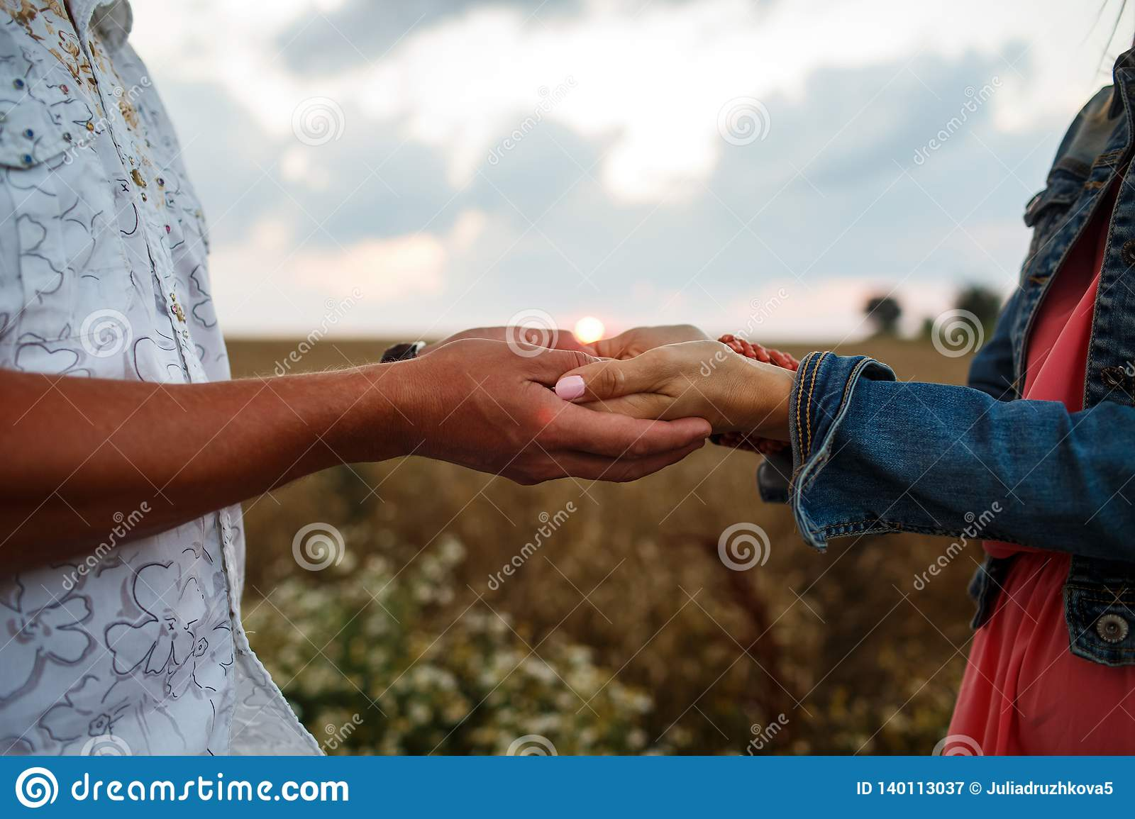 Man and woman holding hands walking in the field at sunset