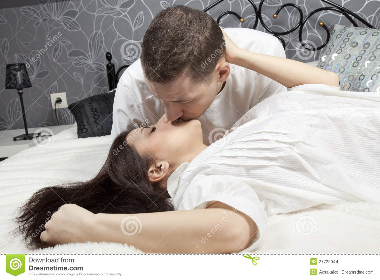 woman and man kissing in bed