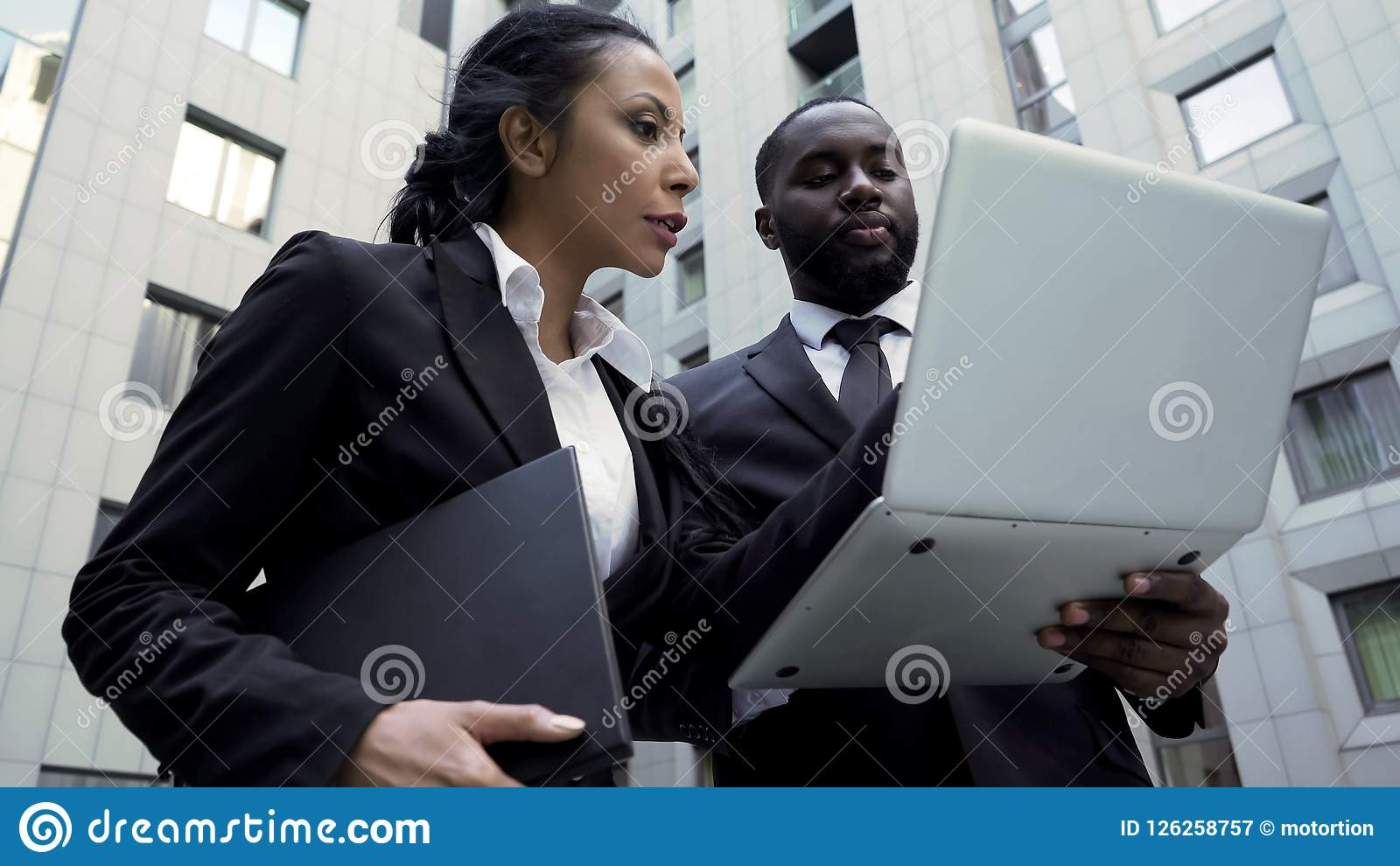 Man and woman looking at laptop outside building, attorneys, brand new evidence