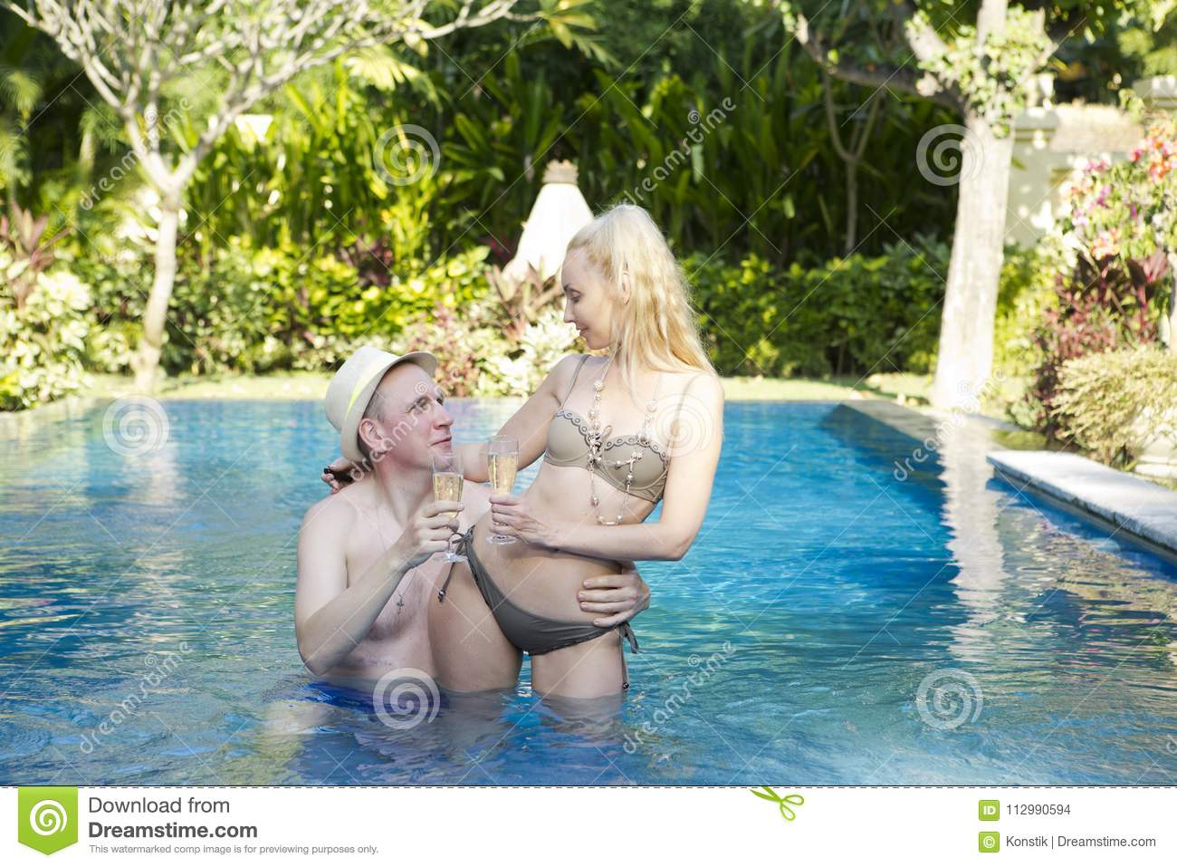 Man and woman, loving couple, in pool in a garden with tropical trees hold glasses with wine in hand