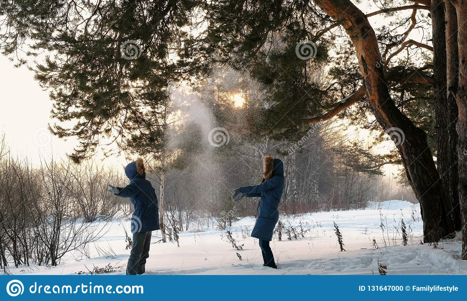 Man and woman playing snowballs in the winter forest. Sunset in the winter forest.